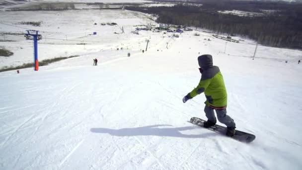 lyžování muž sestupuje na snowboardu za slunečného počasí na zasněženém svahu