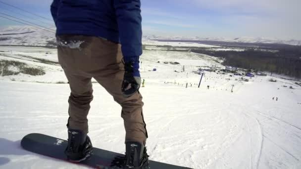 Skifahrer steigt bei sonnigem Wetter auf Schneehang ab