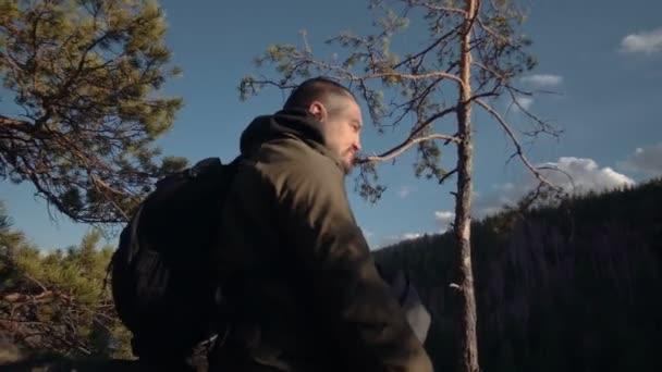 Der Fotograf nimmt Bilder der Landschaft aus den Bergen und dem Fluss bei Sonnenuntergang. ein Mann steht auf einem Hügel und schaut auf das Objektiv der Kamera auf die hohlen, hintere Ansicht