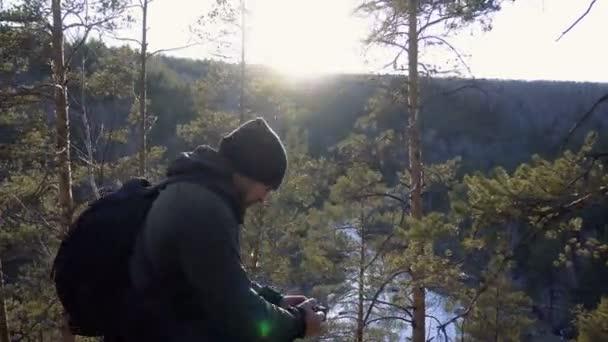 fotografiert der Fotograf die Landschaft von den Bergen und dem Fluss bei Sonnenuntergang. ein Mann steht auf einem Hügel und blickt in die Kameralinse der hohlen Rückansicht
