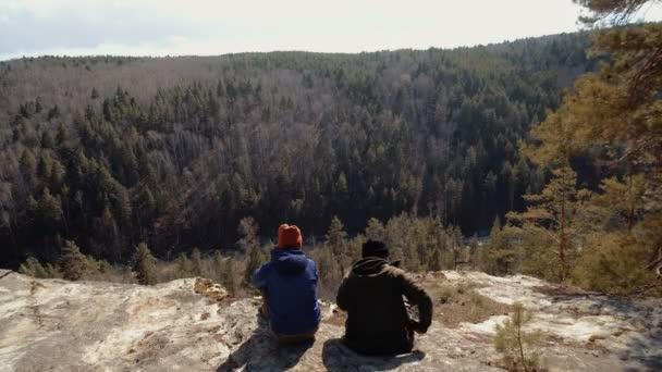 Turisté pár sedí na skále při pohledu na jehličnatého lesa. dobrodružství daleko od domova při západu slunce