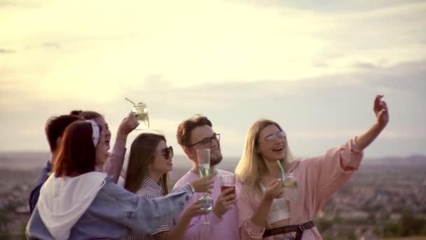 Eine fröhliche Gesellschaft steht auf dem Dach, trinkt Cocktails, hat Spaß und macht Fotos am Telefon. Städtischer Sommercocktail