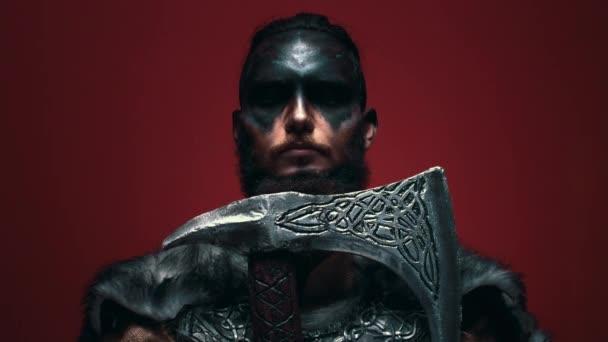 Viking ve válečné barvě si opře vousy o sekeru, otevře oči a agresivně se podívá do kamery. Hrozivý Viking muž na červeném pozadí