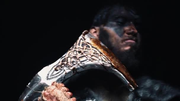 Viking drží sekeru podél štětin. Válečník v bojové barvě se sekerou u tváře. ohnivě červené pozadí