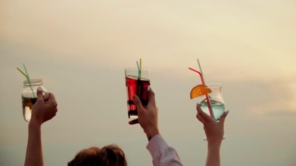 Freunde auf der Party hoben ihre schönen Sommer-Cocktails in die Höhe