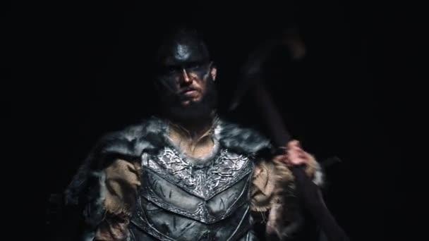 Portrét Vikinga s zakrvácenou hlavou, který si přehazuje sekeru přes rameno a zuřivě křičí do kamery. Posedlý bojovník křičí do kamery šílenýma očima