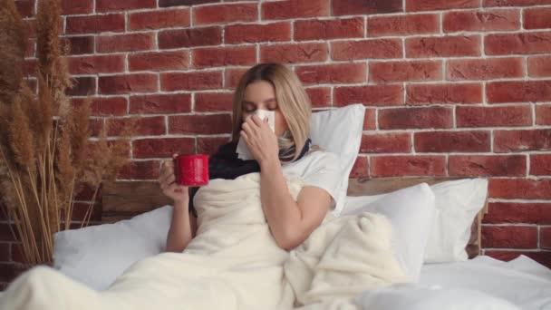 Egy beteg lány sállal a nyakában, egy kényelmes ágyban fekszik egy padlásszerű lakásban. Egy fiatal nő belefújja az orrát egy papírzsebkendőbe, meleg gyógyteát iszik, és orvosi maszkot vesz fel.
