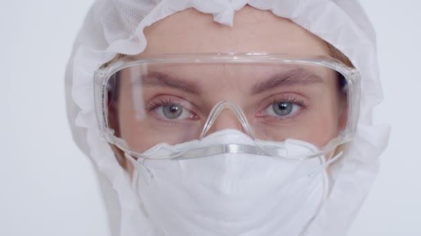 Nahaufnahme der Augen der Mädchen in Atemschutzmaske, Schutzbrille und chemischem Schutzanzug. Eine junge Ärztin blickt in die Kamera