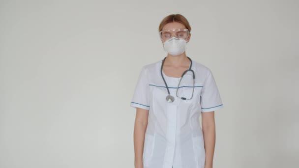 Das Mädchen ist Laborangestellte und faltet selbstbewusst ihre Hände auf der Brust. Ein Arzt mit Stethoskop um den Hals, Atemmaske und Schutzbrille faltet die Hände unter der Brust und schaut.