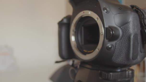 Mužská ruka připevní čočku ke kameře. Připojuji čočku k uchycení kamery. Zblízka připojení fotoaparátu k fotoaparátu stojícímu na stativu