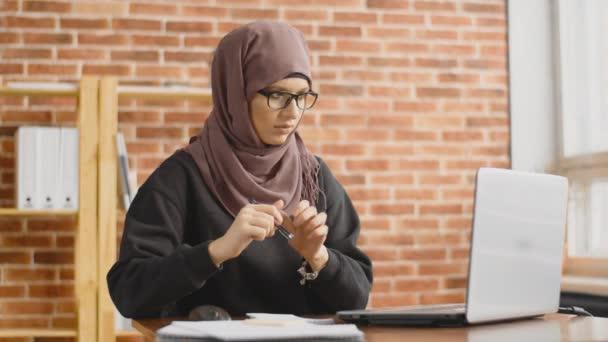 Muslimský student pracující za laptopem. Mladá dívka v hidžábu pracující v kanceláři