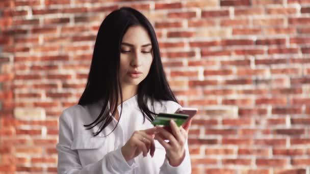 Ein Mädchen mit ernstem Gesicht gibt die Daten der Bankkarte in das Telefon ein. Ein Teenager-Mädchen spendet Geld von einer Bankkarte für wohltätige Zwecke