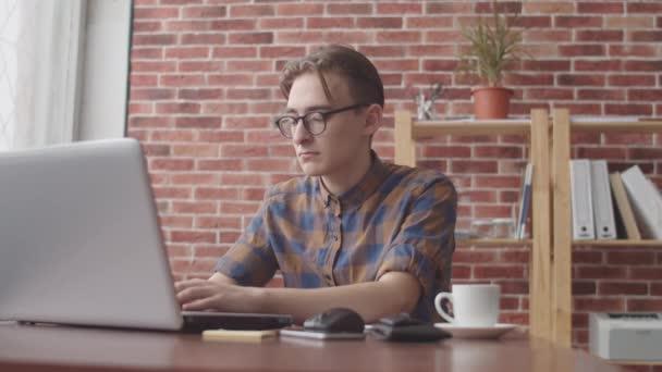 Ein junger Hipster mit Nasenpiercing tippt auf einem Laptop und wendet sich lächelnd in die Kamera. Freiberufler, die am Laptop arbeiten und in die Kamera schauen