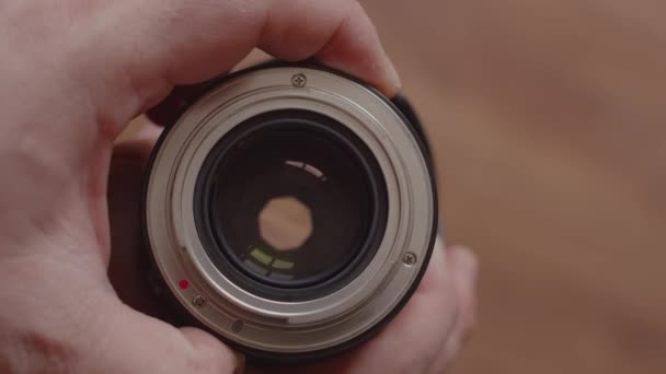 The man holds the lens in his hands, bayonet to the top, and turns the wheel, opening and closing it. Close-up of male hands opening and closing the aperture of the removed lens