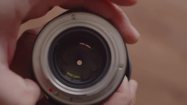 Pohled shora na ruce fotografů, jak kontrolují otevření objektivu a zavírají rychlost závěrky. Muž drží objektiv s objektivem a otáčí kroužkem s rychlostí závěrky.