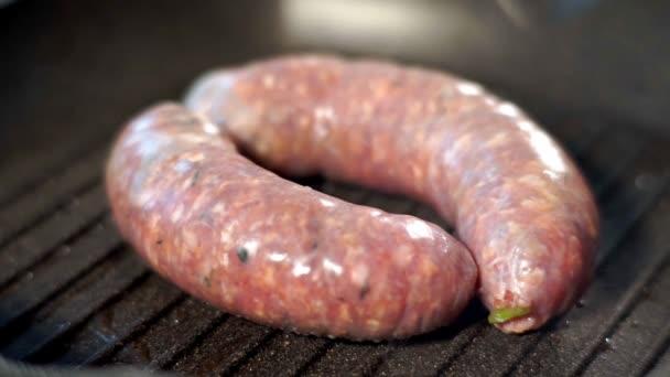 Lahodné a chutné klobásy pro hot dog, smažené v oleji na černém grilu