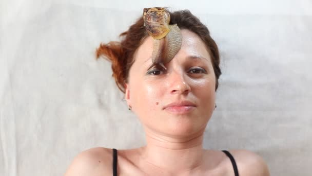 A young woman at the spa receives a facial massage with African snails Achatina. Snails eat dead skin from the produced ones. In the end, it leaves the skin smooth and fresh.