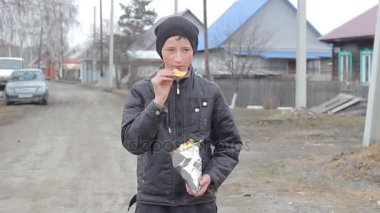 Young teenager in the village eating potato chips