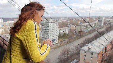 Caucasian women using smart phone. Attractive young woman texting, talking on smartphone on city background