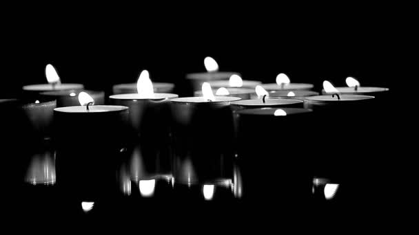 Lots of candles burning in the dark. BW