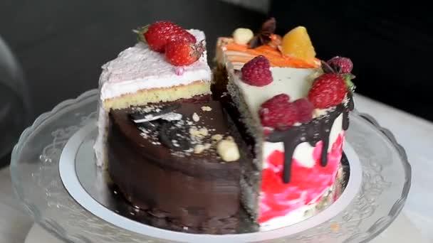 Různé kousky dortu plynule otáčet na základně. Je čokoláda, mrkev, jogurt a bobule.
