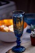 ein Glas Wein oder Wasser aus einem blauen Glas. Warmes Kerzenlicht. Romantisches Dinner