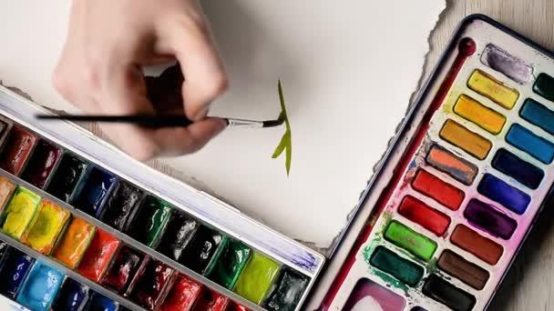 Umělec maluje akvarel barvy na list papíru. Ruce s kartáčem v rámu.
