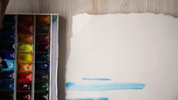 Umělec maluje akvarel barvy na list papíru. Ruce s kartáčem v rámu