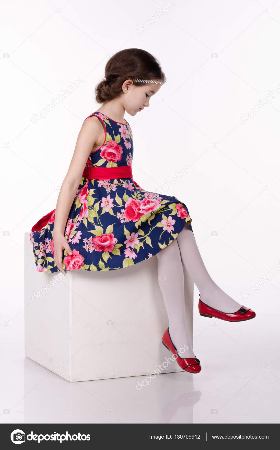Little girl wearing dress with flowers isolated on white background. She is  sitting on the cube. Studio shot. 7