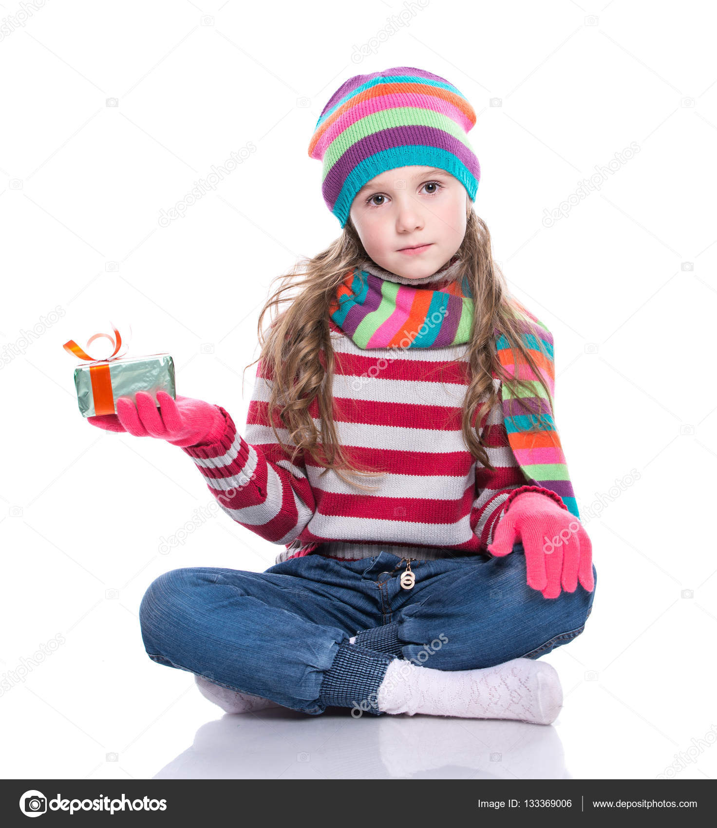 e64d008c3dd8 Smiling pretty little girl wearing colorful knitted scarf, hat and gloves,  holding christmas gift isolated on white background. Winter clothes and  christmas ...