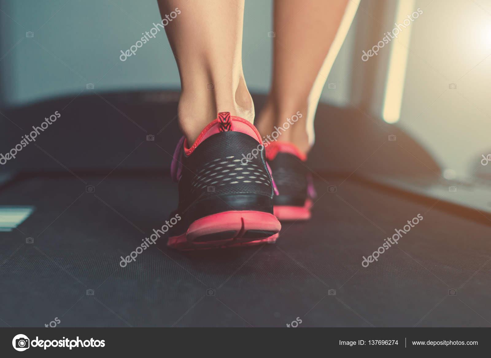 Mujer pies musculares en zapatillas de correr en la caminadora en el ...