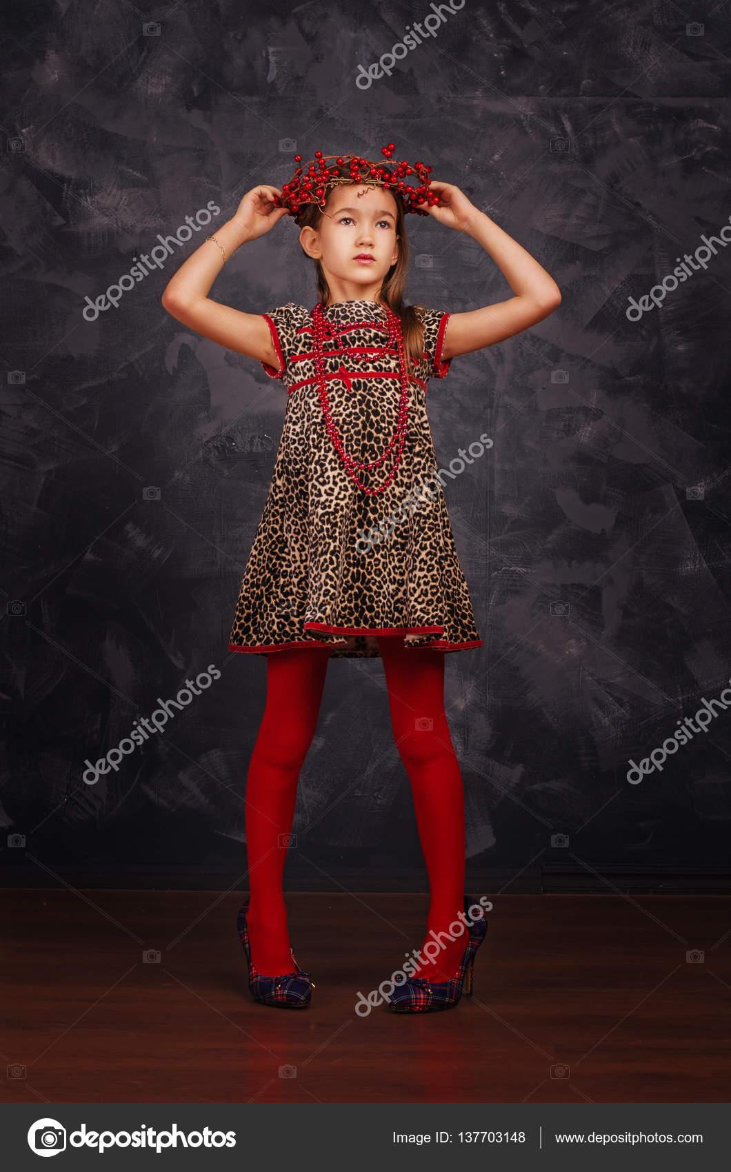 3d2fb6744fa Αρκετά μικρό κορίτσι που φοράει το όμορφο φόρεμα. Φοράει κόκκινο χάντρες  και στεφάνι. Studio που γυρίστηκε– εικόνα αρχείου