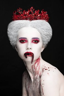 Mysterious beauty portrait of snow queen covered with blood. Bright luxury makeup. Jelly worms in the mouth.
