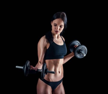 Athletic young woman doing a fitness workout against black background. Attractive fitness girl pumping up muscles with dumbbells.