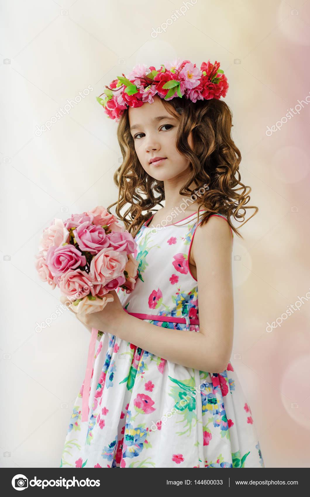 15b5bc4e9ef Πορτρέτο του χαριτωμένο μικρό κορίτσι στο φόρεμα άνοιξη ωραίο, ανθισμένο  στεφάνι στο κεφάλι, κρατά