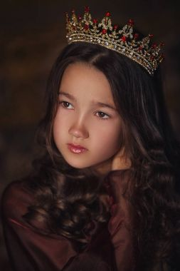 Portrait of cute girl wearing a crown. Young queen or princess.