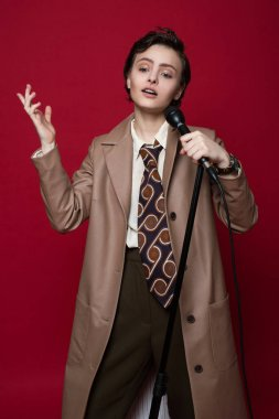 Fashionable beautiful singer girl in retro coat, tie and pants with microphone in hands posing on red background.