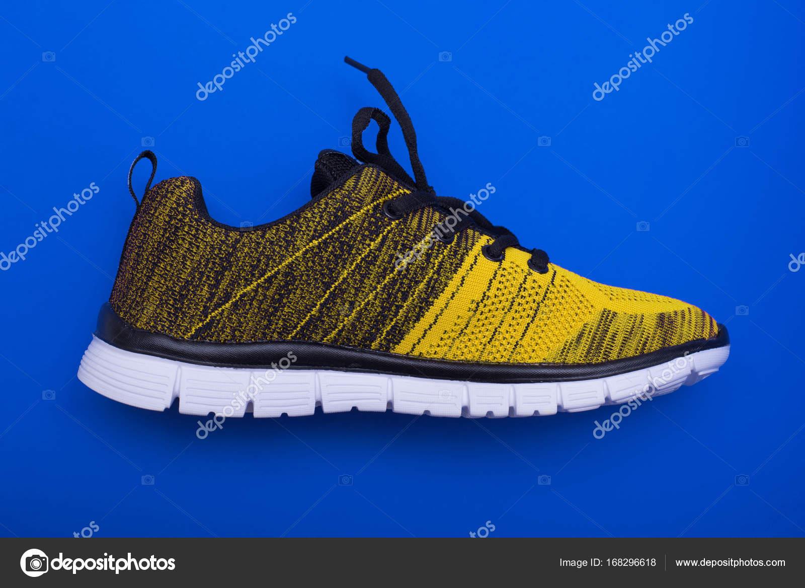 a5f3e59eaa3 Κίτρινο και μαύρο αθλητικά παπούτσια γυναίκα απομονωμένη σε μπλε ...