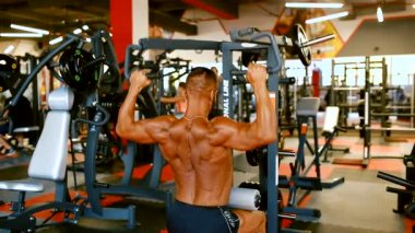 Handsome athlete is exercising in gym centre. Bodybuilder man hard training muscles at training machine.