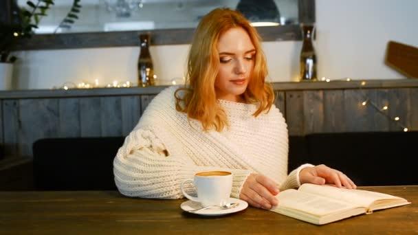 Mladá krásná žena čte knihu v kavárně. Ona se usmívá a těší aroma kávy.