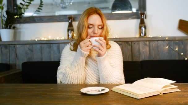 Young beautiful woman is reading a book in cafe. She is smiling and enjoying the aroma of coffee.