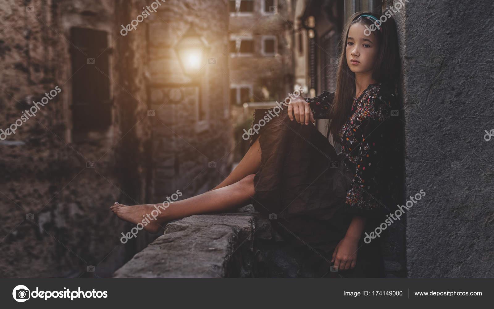 0b9fb650508 Χαριτωμένο νεαρή κοπέλα κάθεται στην οροφή της παλιάς πόλης. Ωραίο θηλυκό  παιδί στην μεσαιωνική πόλη
