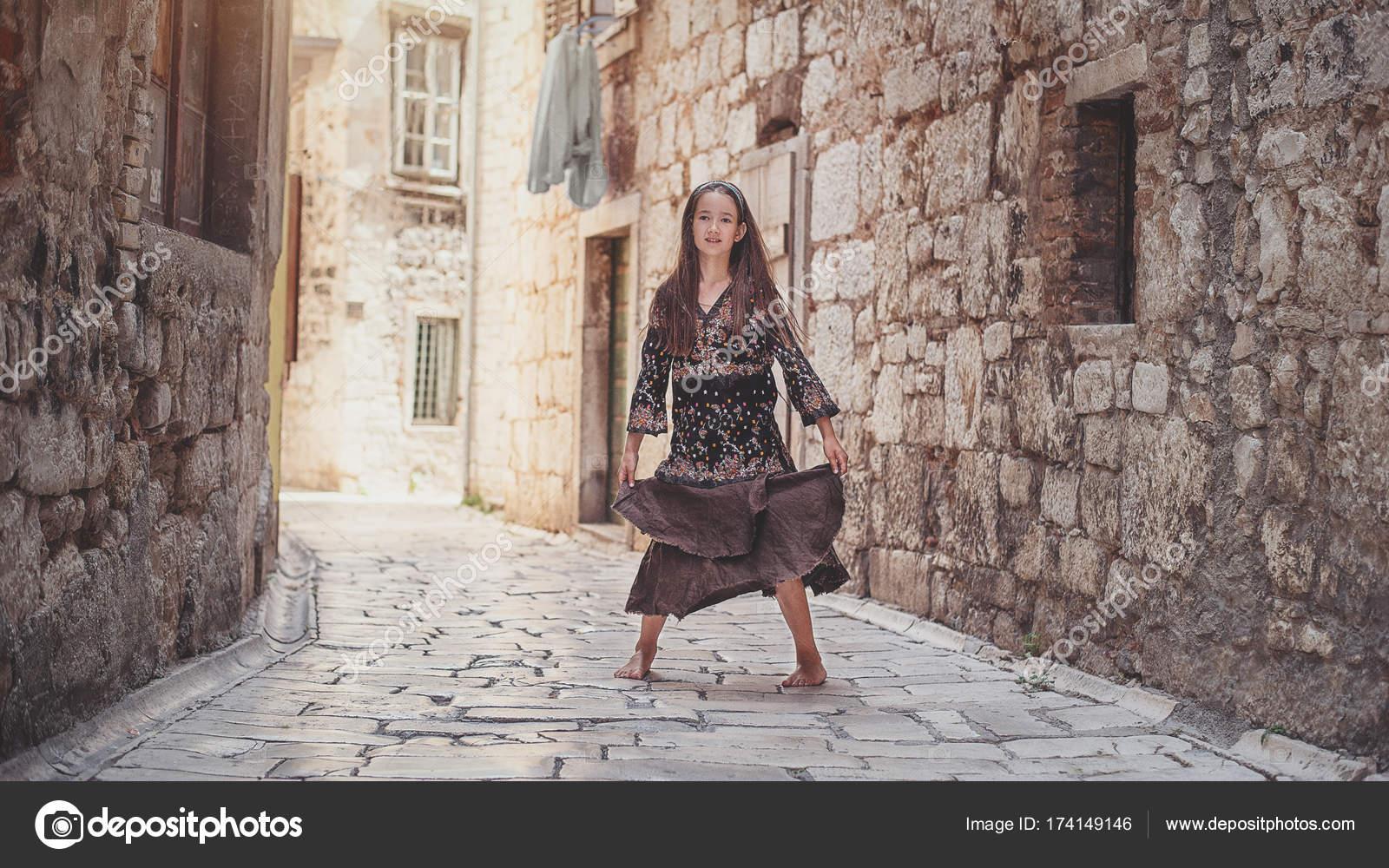 b746687e9a7 Χαριτωμένο νεαρή κοπέλα περπάτημα στην παλιά πόλη. Ωραίο θηλυκό παιδί στην  μεσαιωνική πόλη — Φωτογραφία