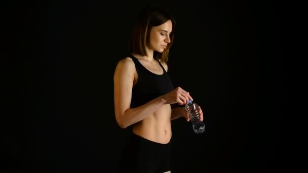 Giovane donna atletica in acqua potabile sportswear in studio su sfondo nero. Figura sportivo ideale femminile. Ragazza di forma fisica con perfetto corpo muscoloso e stretto scolpito.