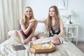 Két boldog lány pizsama bachelorette párt együtt tölteni az időt és a pizzát eszik az ágyban.