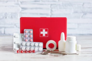 First aid kit red box with medical equipment and medications for emergency on white wooden background.