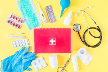 First aid kit red box with medical equipment and medications for emergency top view on pastel yellow background.
