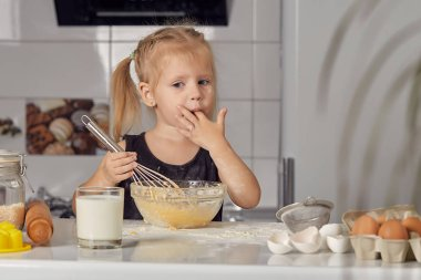 Little little girl prepares a sweet cake with flour, milk, sitting on chairs at a table in a modern kitchen. Girl holds a whisk, stirring eggs in a bowl, prepares pancake dough. Little cook.