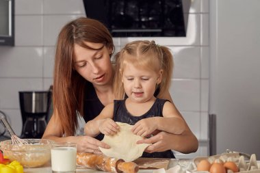 Mother and daughter preparing a sweet cake using flour, milk, sitting on chairs at a table in a modern kitchen. Girl holding a whisk, stirring eggs in a bowl, preparing pancake dough with her mom.