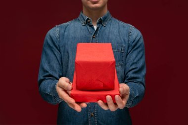 Young man holding red giftbox isolated over red background.